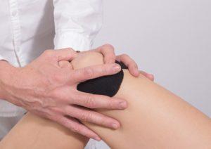 Arzt untersucht schmerzhaftes Knie